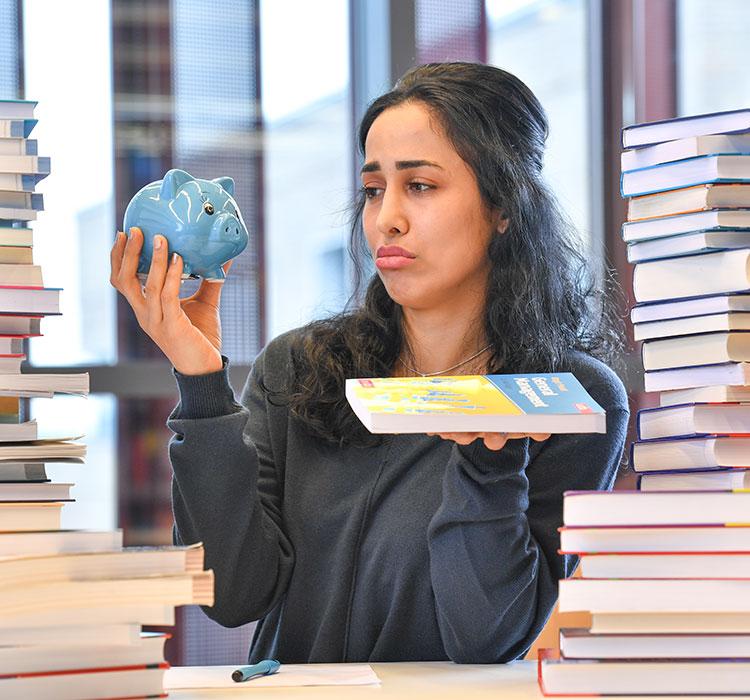 Eine Studentin schaut traurig auf ein Sparschein